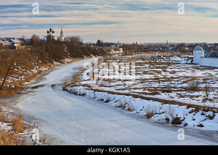 City landscape of Suzdal. River, ice-bound, In the flood plain lies snow. On the slope of the hill, the snow melted - Stock Photo