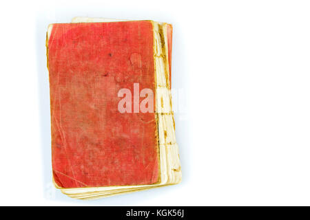 Old antique worn book with red stained cover on white. Vintage thread sewn print publication with torn out spine - Stock Photo