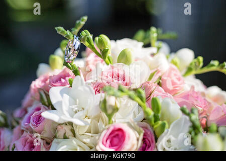 Two Smooth Shiny Wedding Rings On A Pink And White Roses Bouquet Taken Outdoor