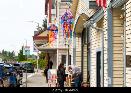 A women tourist watching a man working at a wood lathe outside a shop in Sitka, Alaska. - Stock Photo