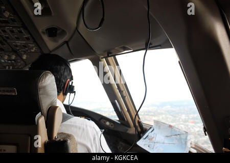 Pilot sitting on a jumpseat in flight deck with headphones, communicating with tower, looking through a aircraft - Stock Photo