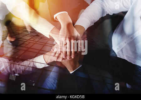 Business people joining hands in the office. concept of teamwork and partnership. double exposure - Stock Photo
