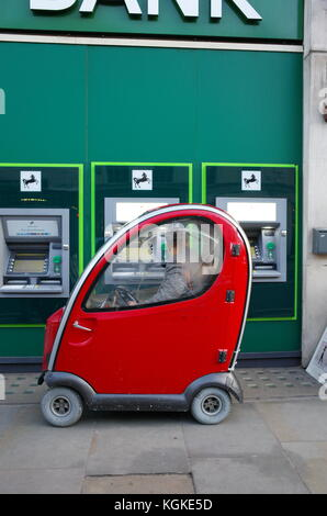 man in red Shoprider mobility scooter using cashpoint ATM outside Lloyds Bank in London, England - Stock Photo