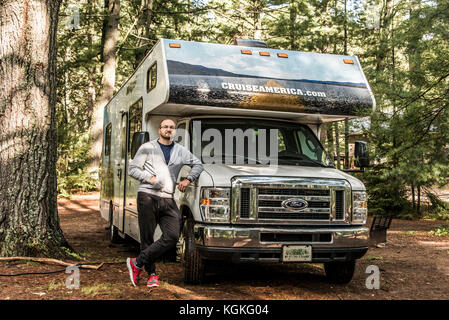 Canada Ontario Algonquin National Park 30.09.2017 - man in front of Parked RV camper car at Lake of two rivers Campground - Stock Photo