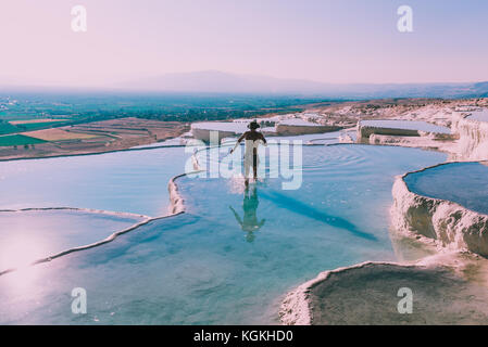 Unidentified man walks at Pamukkale (Cotton Castle) that is popular with Travertine pools and terraces  where people - Stock Photo