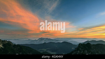 Mountain landscape at sunset in Julian Alps. Amazing view on colorful clouds and layered mountains. - Stock Photo