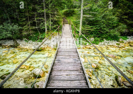 Old wooden plank bridge across beautiful river. Overcoming an obstacle concept. Stock Photo