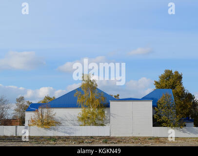 The building with siding and blue metal-plastic roof made of corrugated iron - Stock Photo