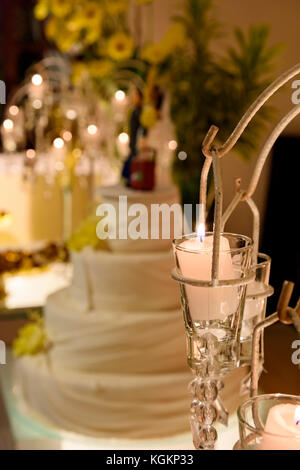 Detail of whole wedding table decorated with hanging candles and flowers and cake in the background - Stock Photo