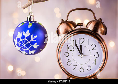 Vintage Copper Alarm Clock Showing Five Minutes to Midnight. New Year Countdown. Blue Christmas Tree Ball with Ornament Hanging on Branch. Glittering