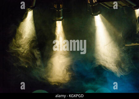 Stage lights shine through smoke. - Stock Photo