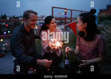 Happy male and female friends holding sparklers on patio - Stock Photo