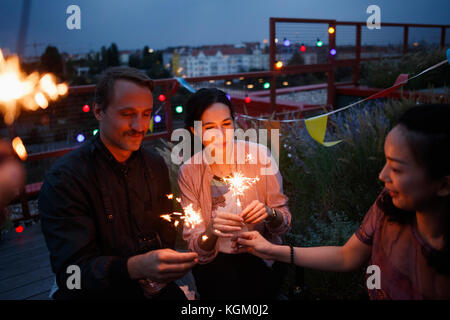 Male and female friends holding sparklers on patio - Stock Photo