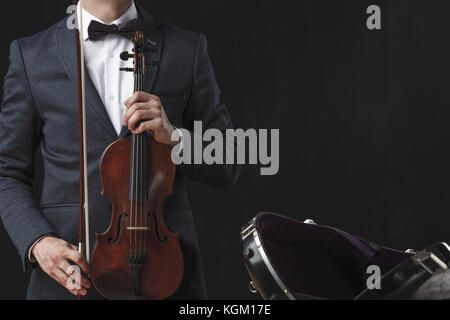 Midsection of man holding violin while standing by case against black background Stock Photo