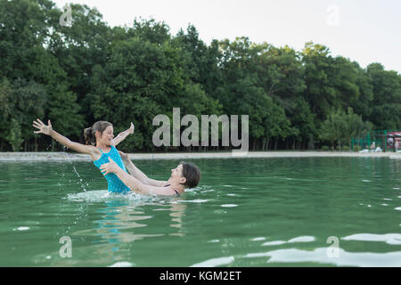 Grandmother enjoying with granddaughter in swimming pool against trees - Stock Photo