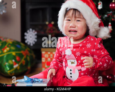 crying baby girl missing her christmas gift - Stock Photo
