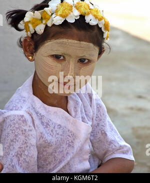 Young girl poses wearing traditional thanaka in Bagan, Myanmar - Stock Photo