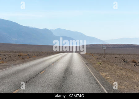 Empty desert road. Death Valley Badwater Road with Badwater Basin shimmering in the distance. - Stock Photo