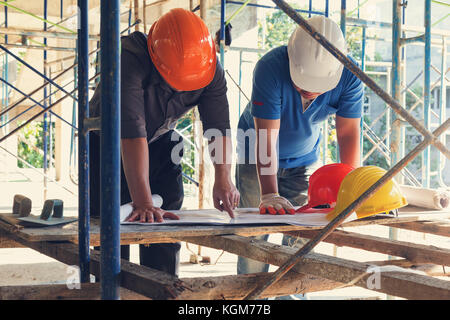 Construction concepts, Engineer and Architect working at Construction Site with blueprint, Vintage Effect - Stock Photo