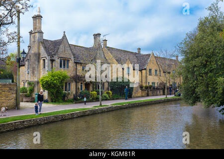 Bourton On The Water, England - 7 April 2017 - Locals and tourists spend and enjoy their leisure time along the - Stock Photo