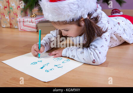 Little girl preparing the Santa Letter. She painting the gifts she want. Pre-reader concept - Stock Photo
