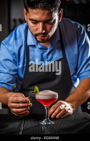 Bartender is decorating cocktail with mint leaf - Stock Photo