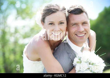 Groom giving piggyback ride to bride in countryside - Stock Photo