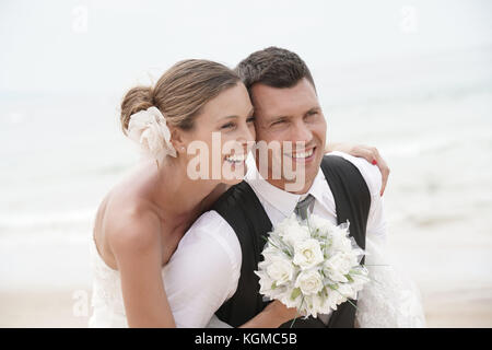 Groom giving piggyback ride to bride on the beach - Stock Photo