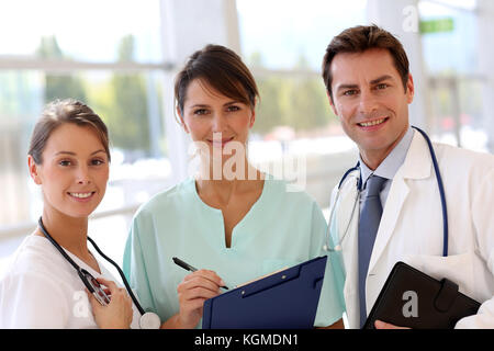 Smiling medical team standing in hall - Stock Photo