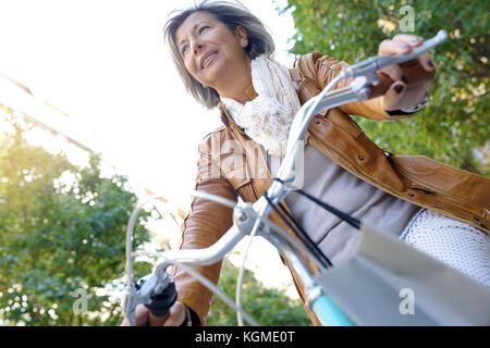 Portrait of senior woman riding city bike - Stock Photo
