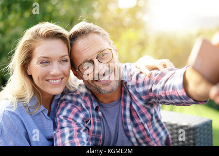 Portrait of cheerful mature couple taking selfie picture - Stock Photo