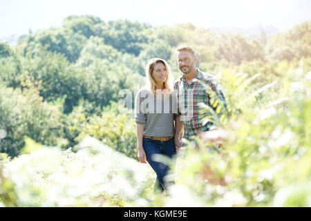 Happy mature couple walking in countryside on sunny day - Stock Photo