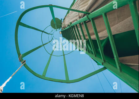 High green metal ladder on the construction site. Original angle first person perspective view - Stock Photo