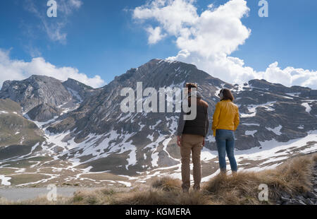 Happy joyful young couple walking on the foothills together. - Stock Photo