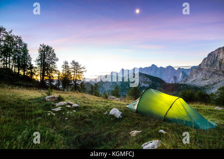 A tent glows under a moon night sky at twilight hour. Alps, Triglav National Park, Slovenia. - Stock Photo