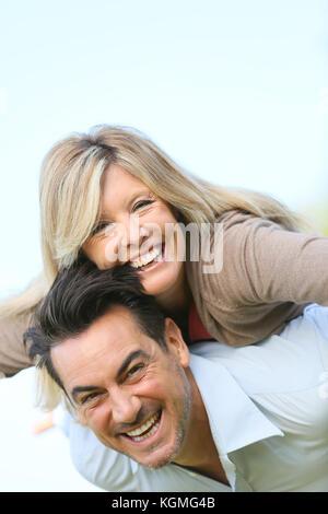Cheerful mature man giving piggyback ride to woman - Stock Photo