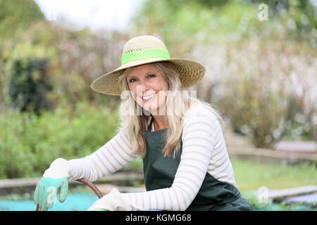 Portrait of smiling woman in vegetable garden - Stock Photo
