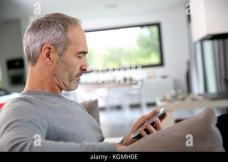 Senior man in couch reading message on smartphone - Stock Photo
