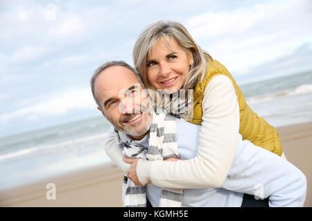 Senior man giving piggyback ride to wife - Stock Photo