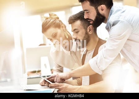 Trendy business team meeting in front of desktop - Stock Photo