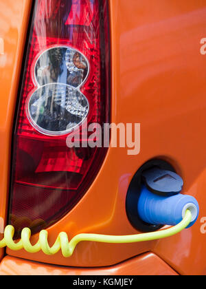 Electric car connected to a charger via a cable - Stock Photo