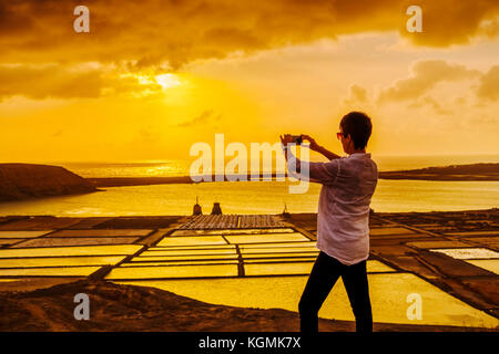 Saltworks. Woman taking a photograph at sunset in Salinas de Janubio. Lanzarote Island. Canary Islands Spain. Europe - Stock Photo
