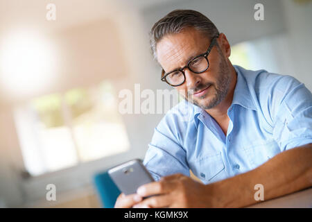 Mature man with eyeglasses typing message on smartphone - Stock Photo