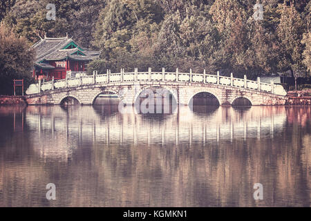 Retro toned picture of Suocui Bridge by the Black Dragon Pool in Jade Spring Park, Lijiang, China. - Stock Photo