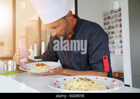 Chef in private kitchen preparing special pasta dish - Stock Photo
