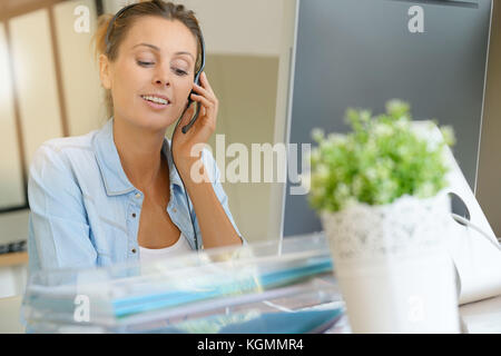 Customer service operator talking on phone in office - Stock Photo