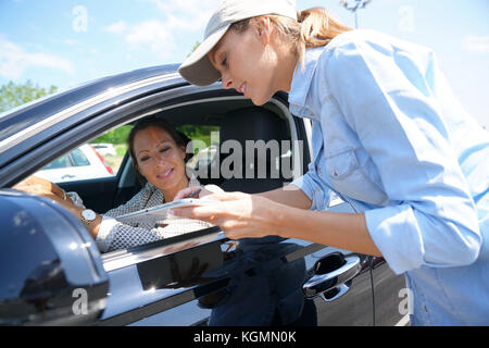 Woman stopping car driver for customer survey - Stock Photo