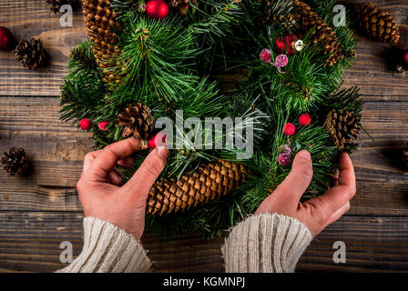 Preparation for xmas holidays. Woman decorating christmas green wreath with pine cones and red winter berries and - Stock Photo