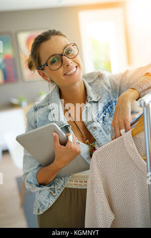 Cheerful clothing salesperson standing in shop Stock Photo ...