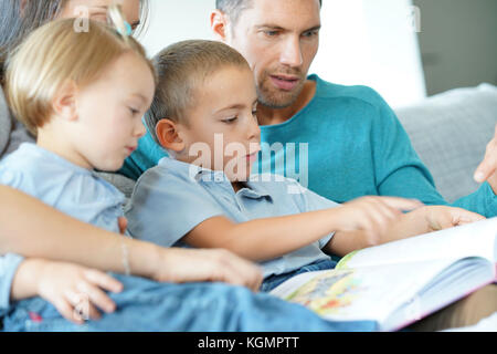 Family sitting on sofa reading book with kids - Stock Photo